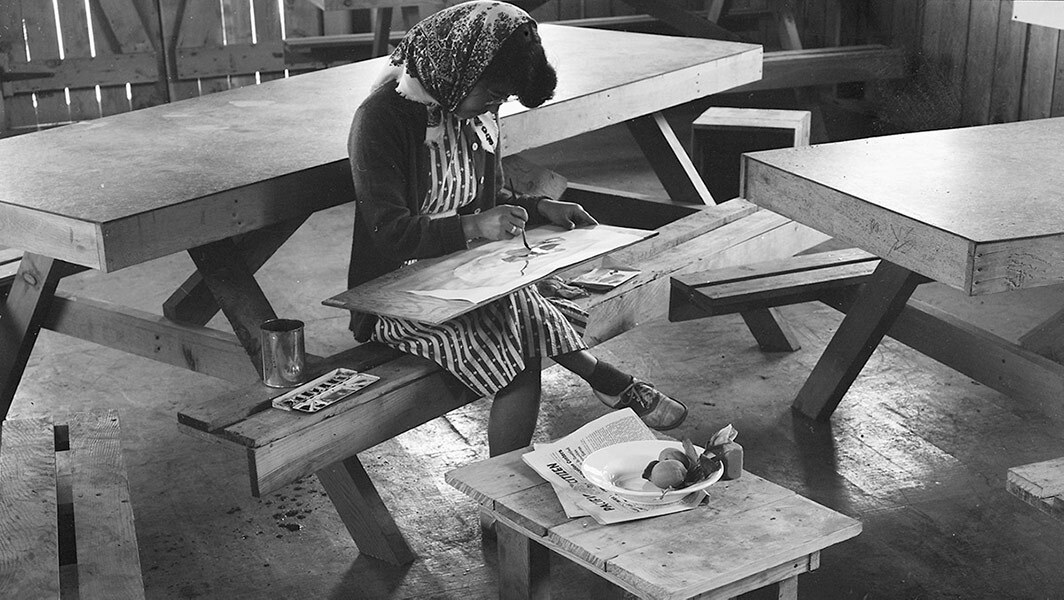 A black and white photo of a Japanese American woman with a bandana on her head painting a watercolor on a wooden table.