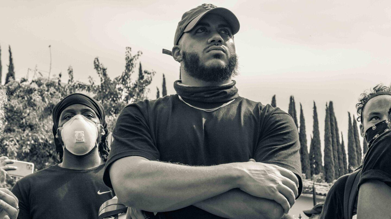Issac Bryan stands arms folded, at a Black Lives Matter in June 2020 | Trevor Jackson