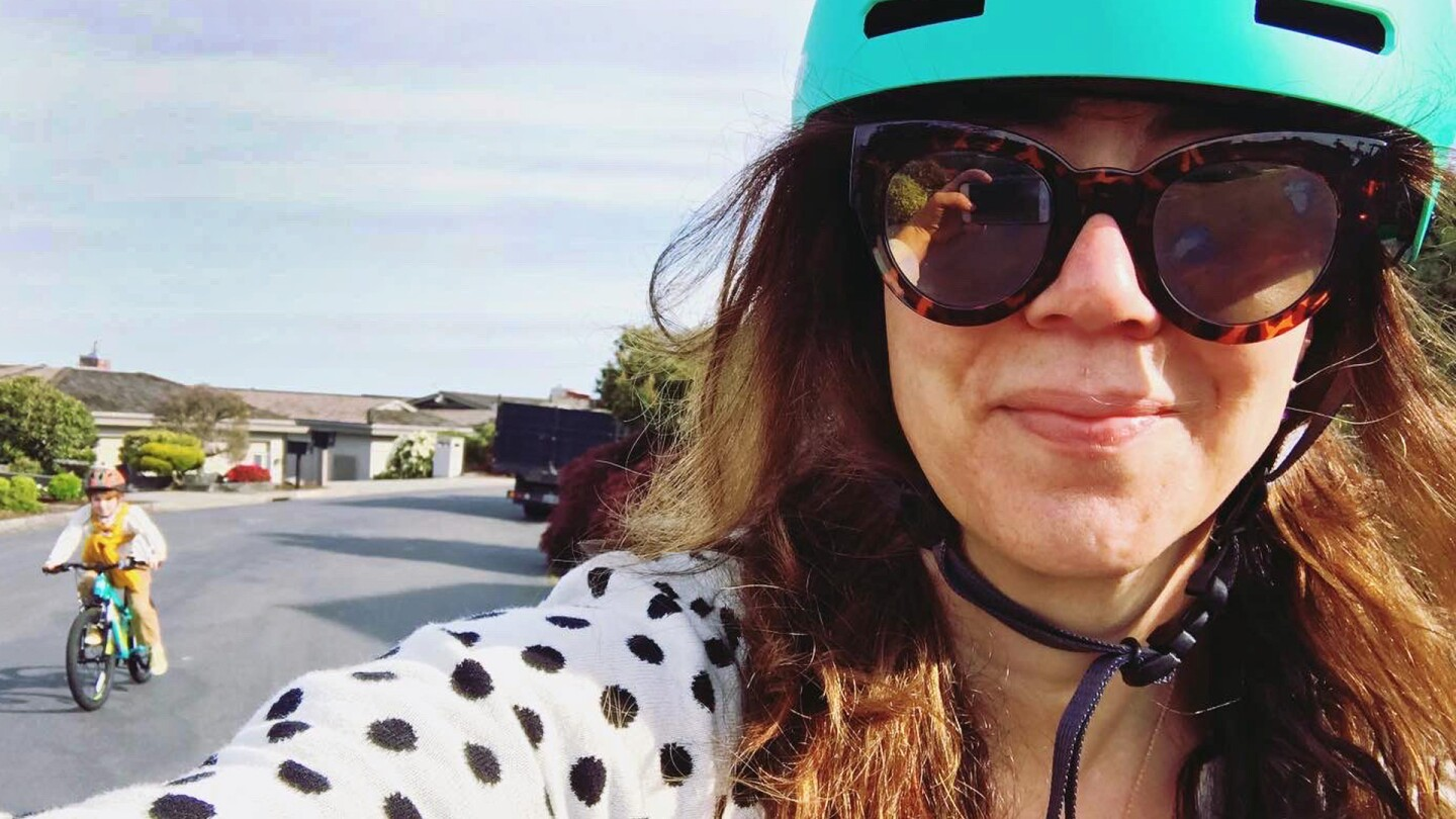 Woman wearing a bicycle helmet takes a selfie with someone riding a bike behind her.