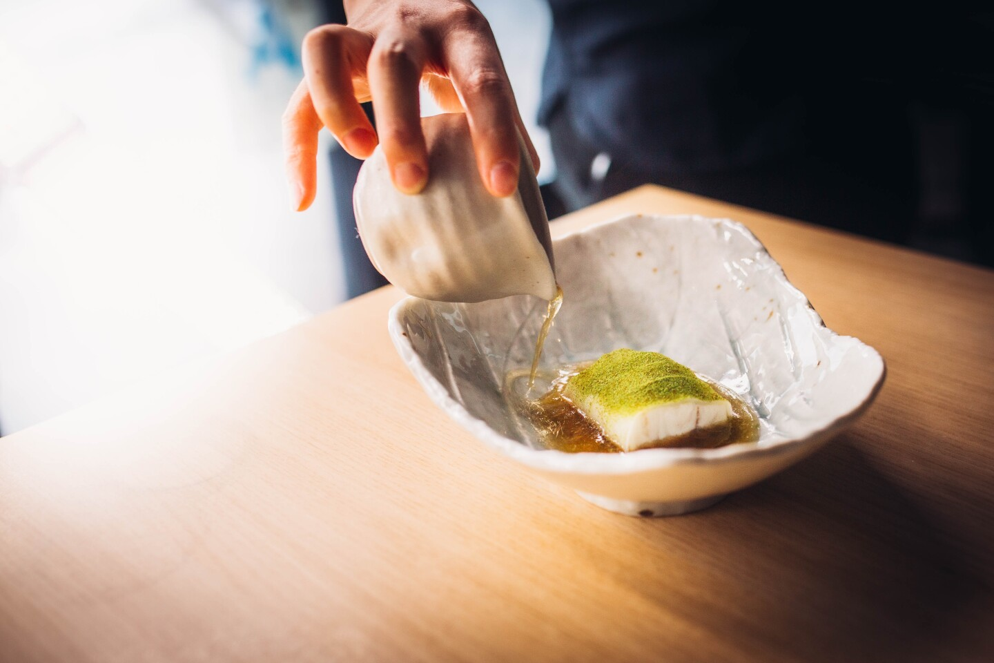 An asymmetrical ceramic dish holds a small, bite-sized piece of white steamed fish sitting in a thin, broth-y sauce. The fish is topped with a fine green powder. Additionally, someone is pouring more of the sauce from a small ceramic container.
