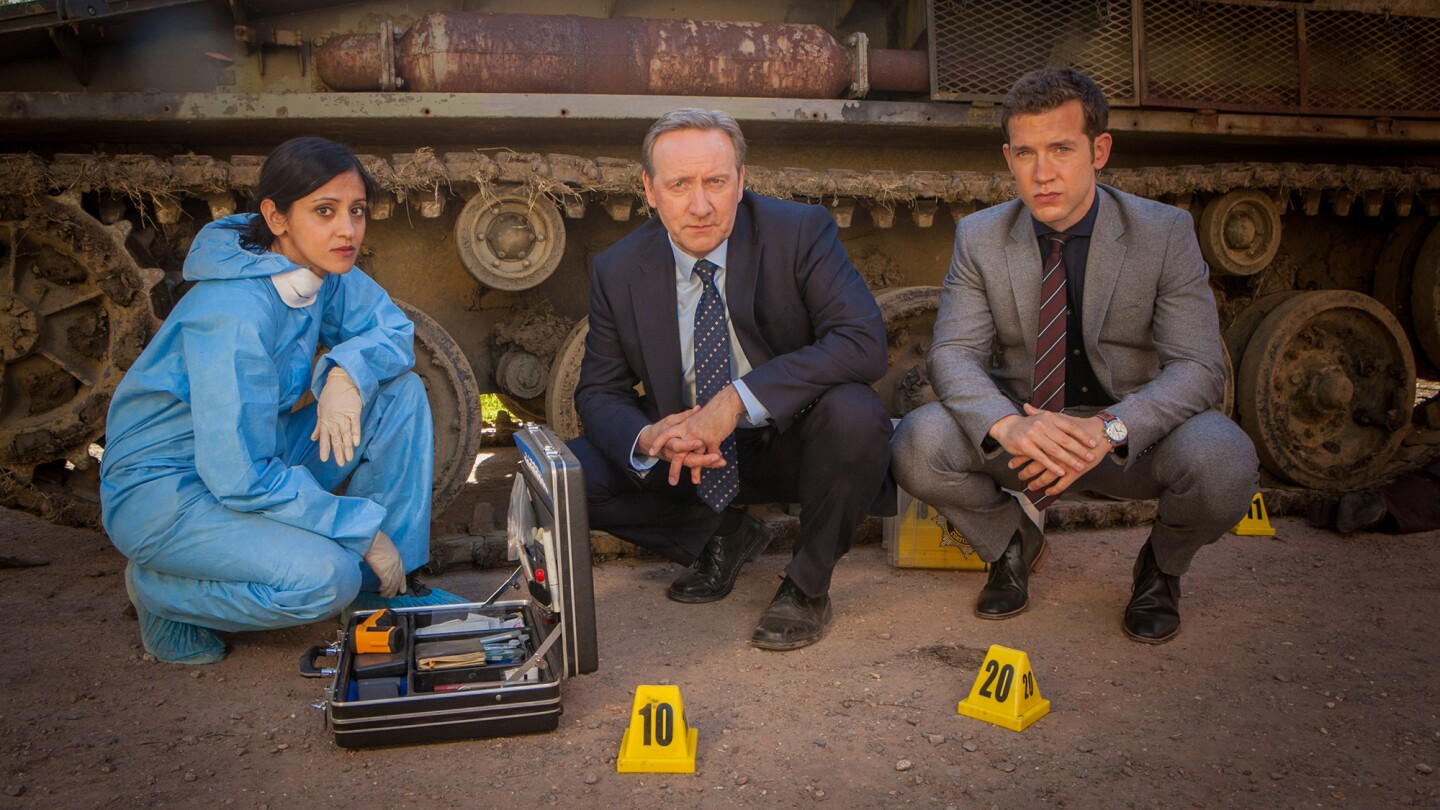 """Stars of """"Midsomer Murders"""" crouch down on the floor while looking into the camera."""