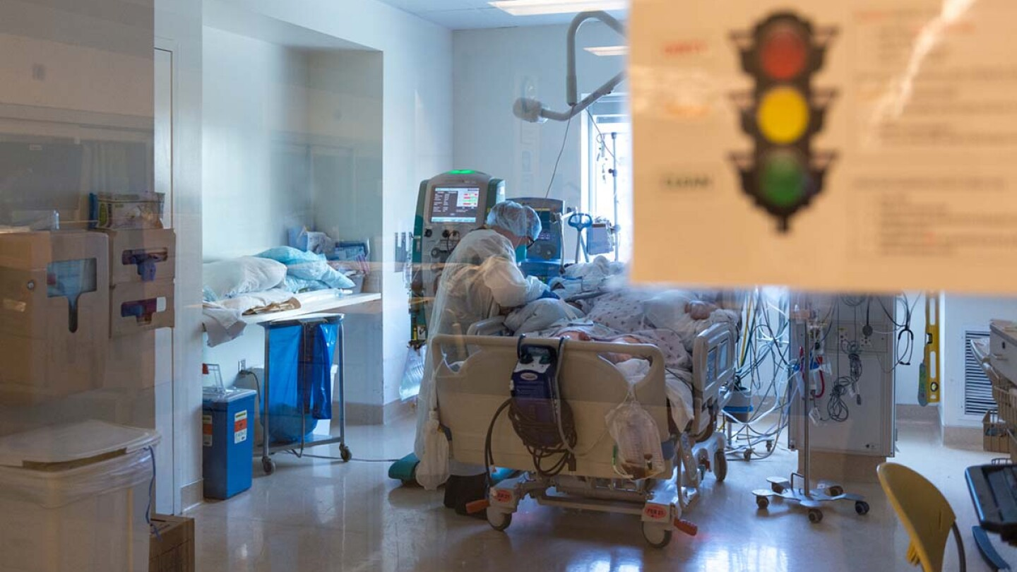 Nurse Yvonne Yaory checks on a coronavirus patient who is connected to a ventilator. | Heidi de Marco/California Healthline
