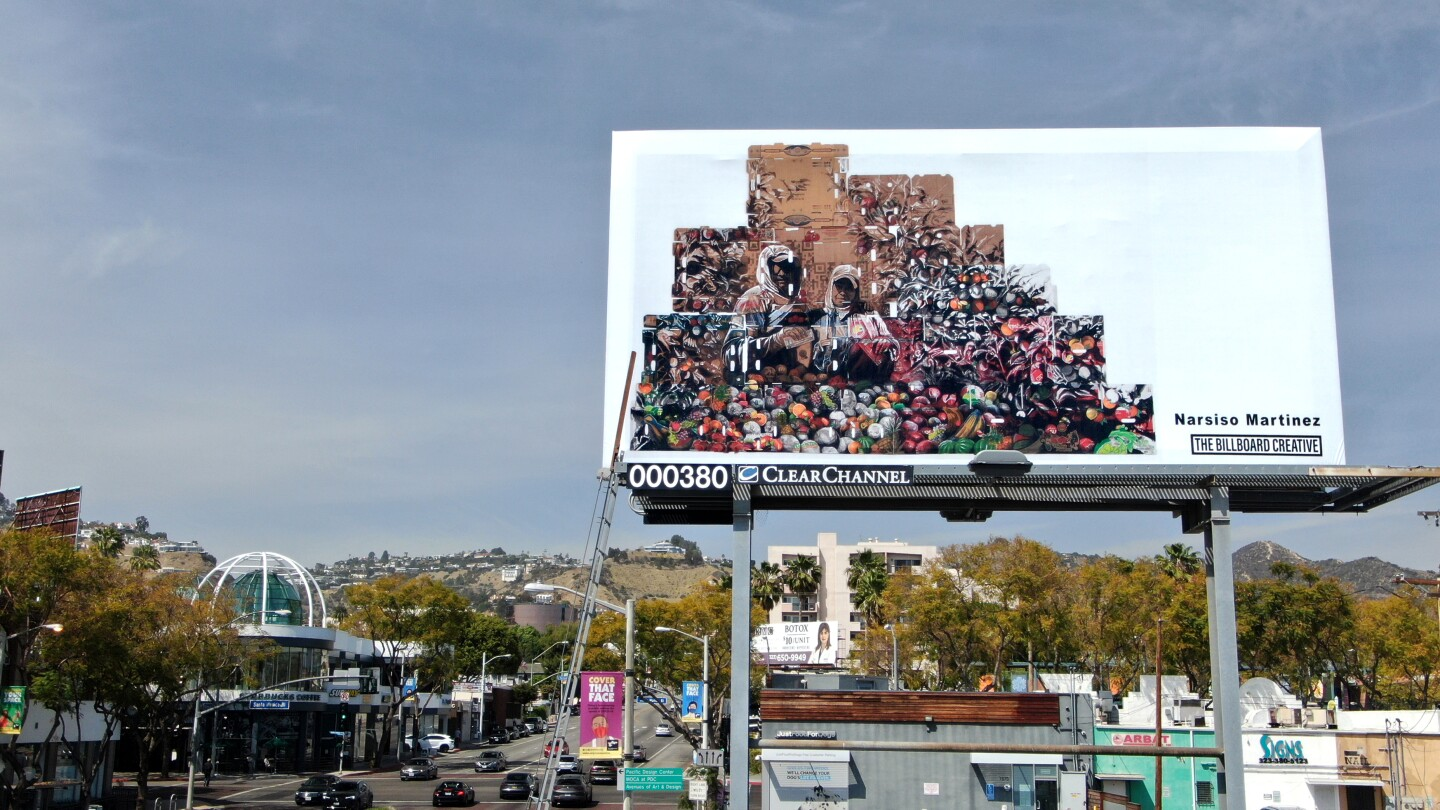 A billboard shows two farmworkers superimposed against piles of produce and the wooden crates used to transport them.