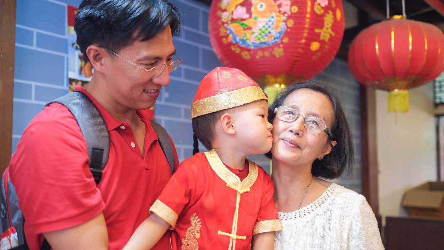 A father holding a t odder who kisses grandma as they celebrate Lunar New Year. | iStock