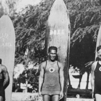 Three men standing in front surfboards | Still from Lost LA Season 3 Beach Culture