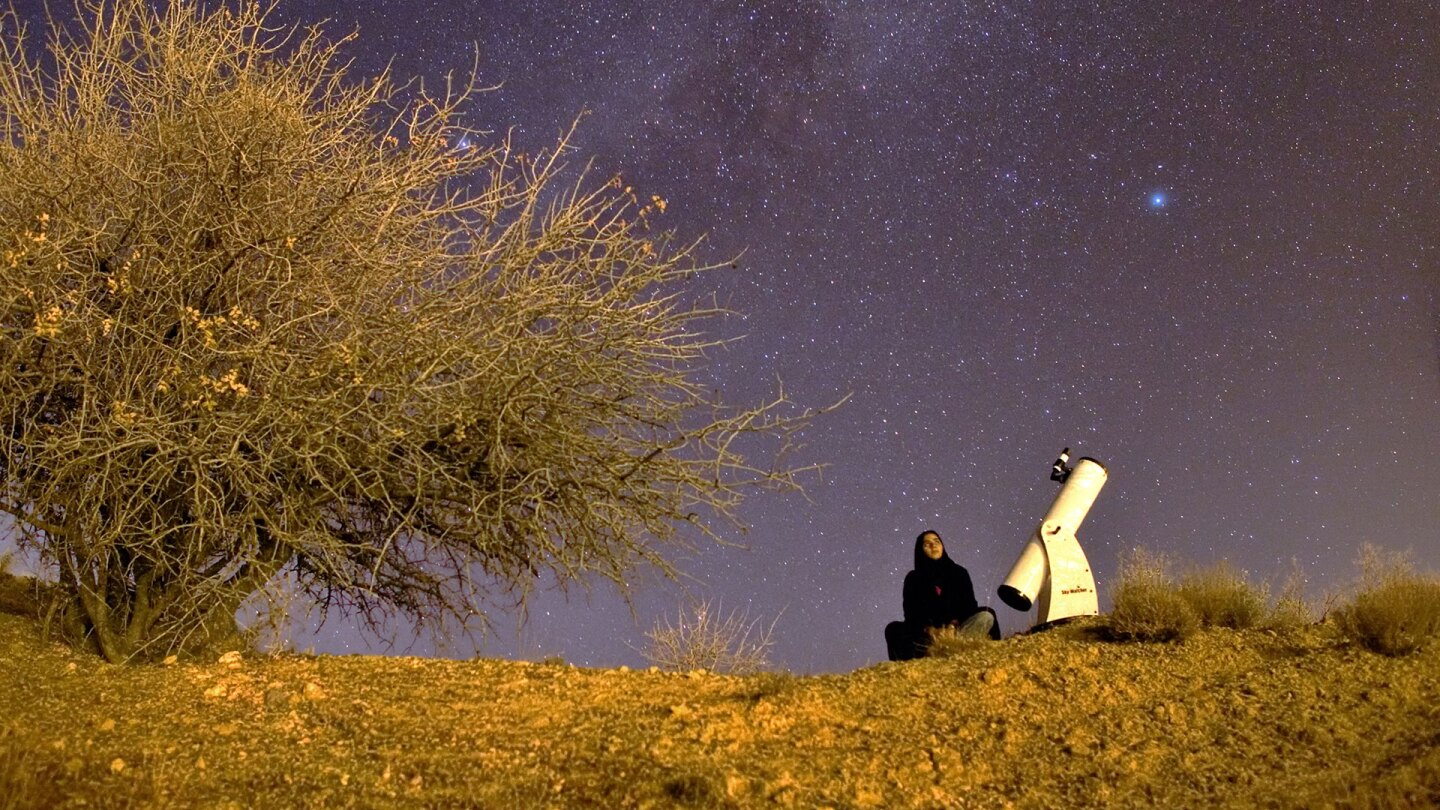 Sepideh sitting atop a mountain between a telescope and large tree. | Sepideh