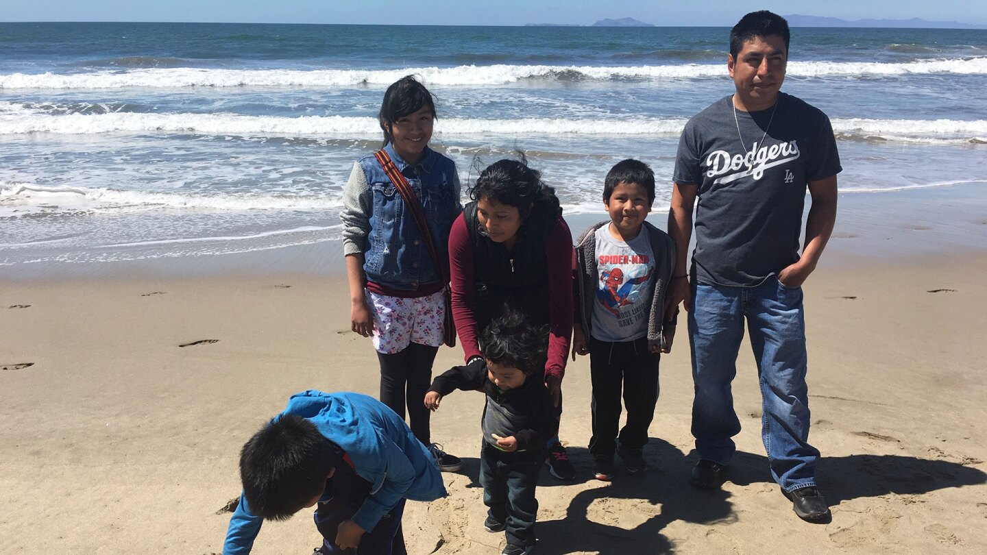Tello family standing at the beach with Jordi (foreground), who is drawing a ninja in the sand.   Pilar Marrero
