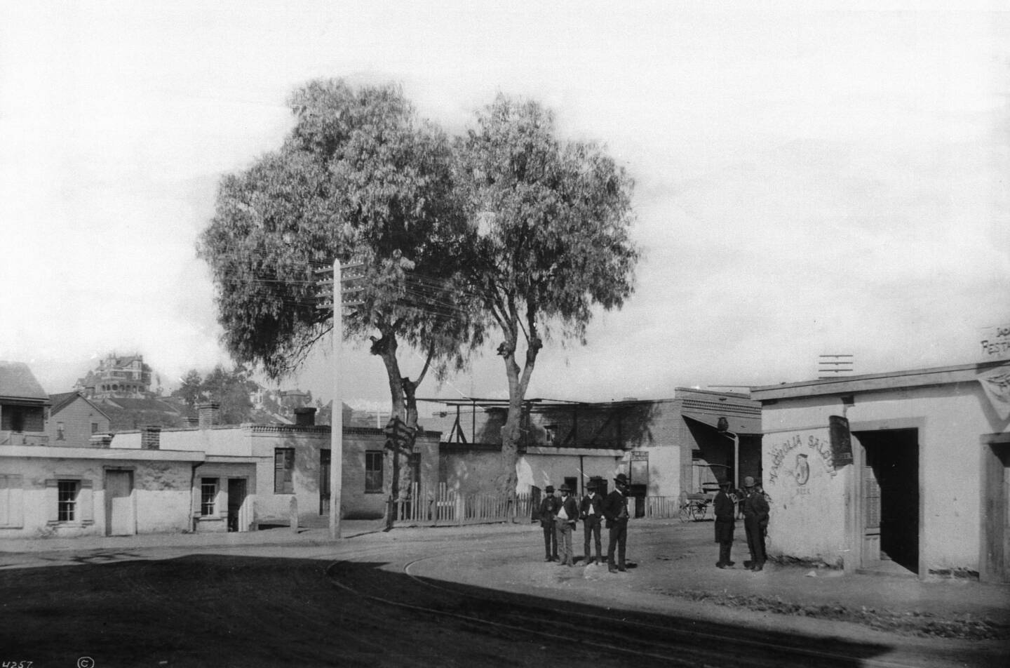 Six men stand ouside of the Magnolia Saloon at New High Street and Marchessault Street, Sonora Town, 1885-1887