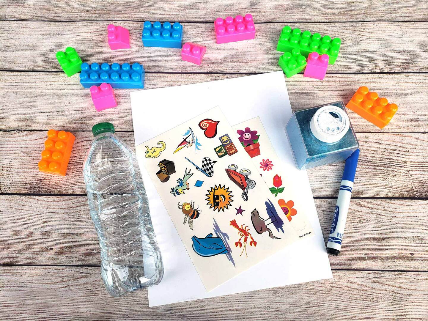 An empty plastic water bottle is laid out on a table alongside plastic blocks, stickers, a sheet of paper, a marker and a glitter container.