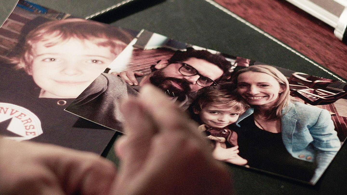 A hand hovers over pictures laid on the table.