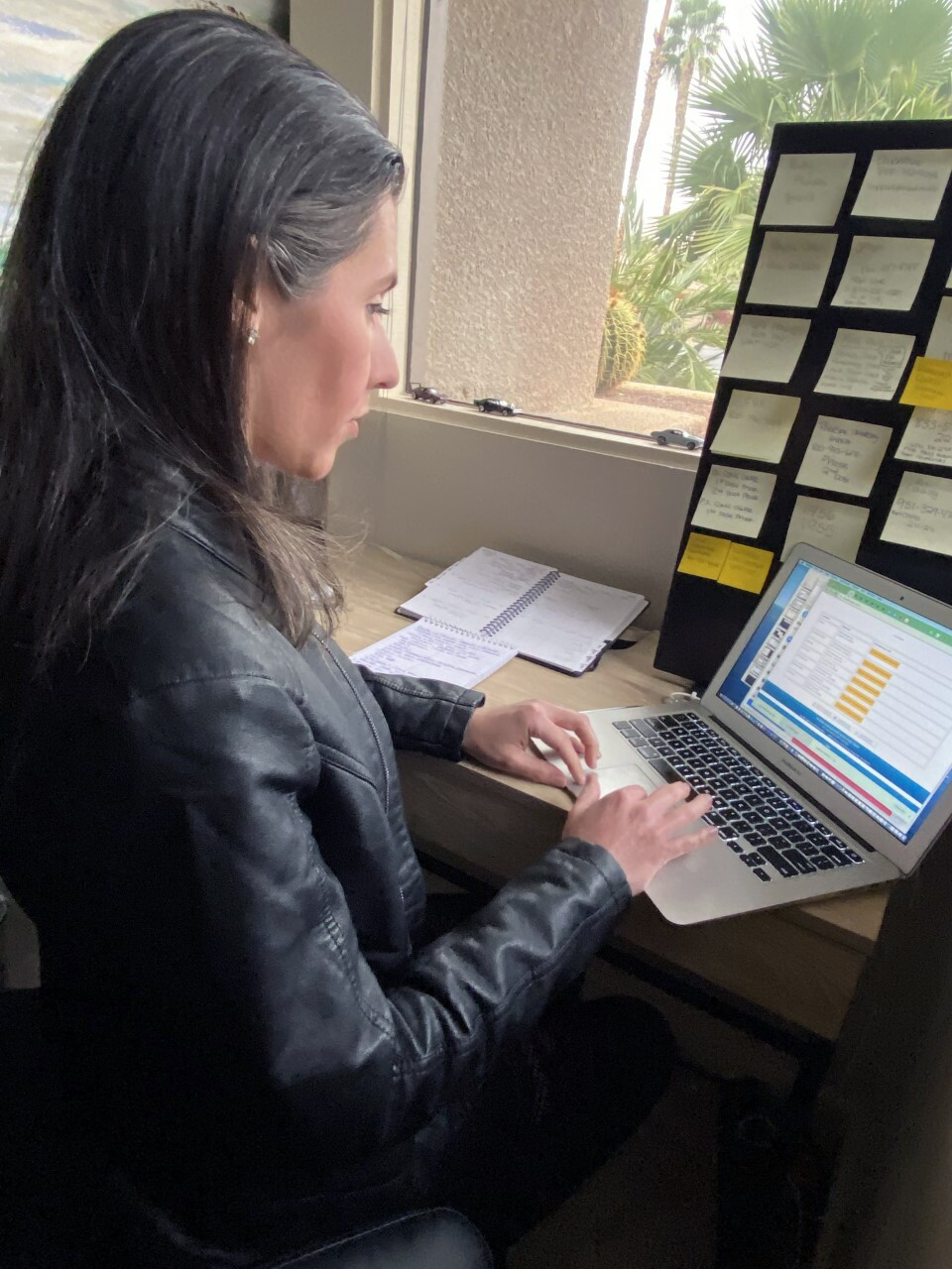 A woman in a black jacket and long gray hair types on a laptop.