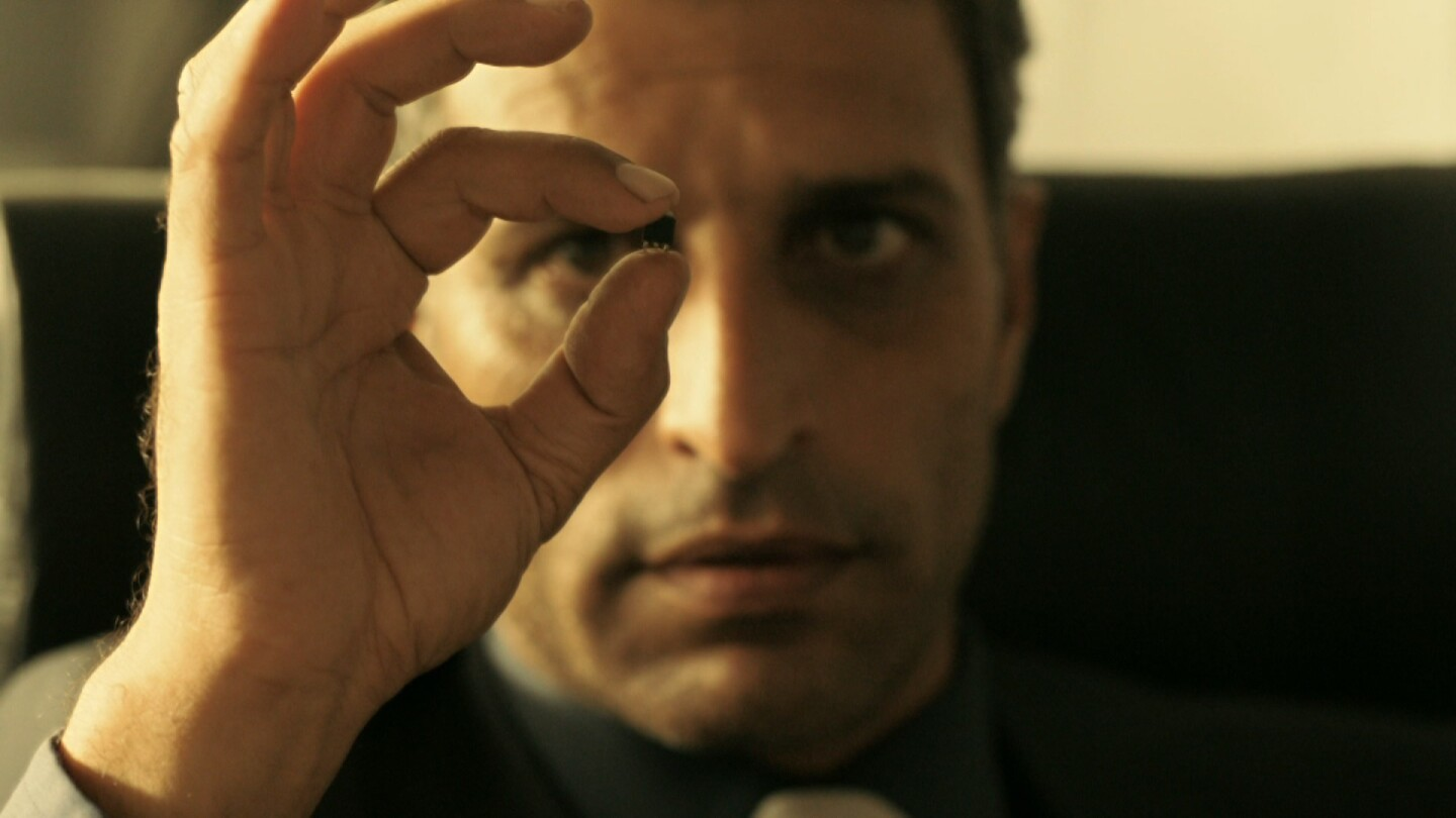 """A man stares at something small held between his fingers from """"Fauda: S2 E10."""""""