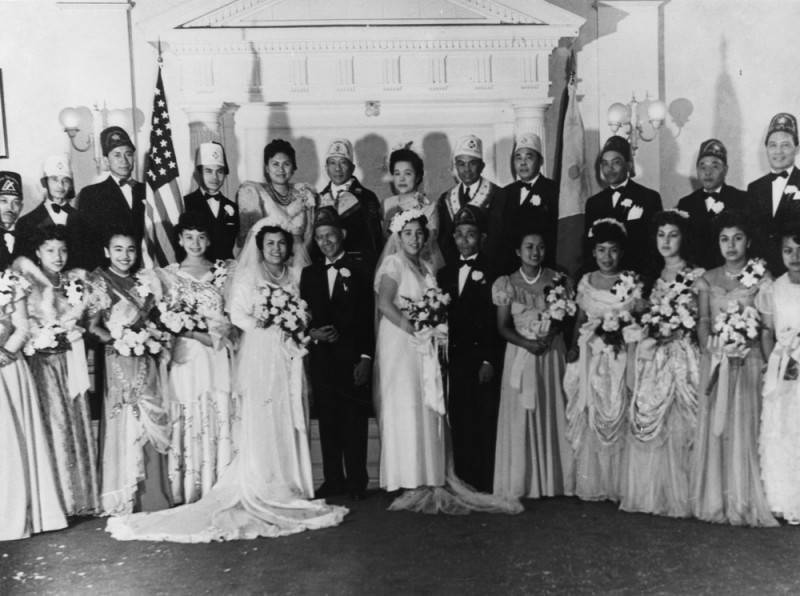 Black and white image of two brides and two grooms standing next to their bridal parties