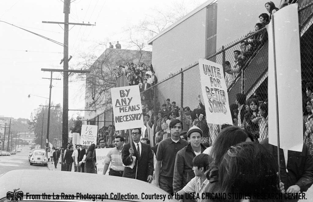 """CSRC_LaRaza_B1F3C3_DW_020 Man holds a """"by any means necessary"""" poster at Roosevelt Walkouts 