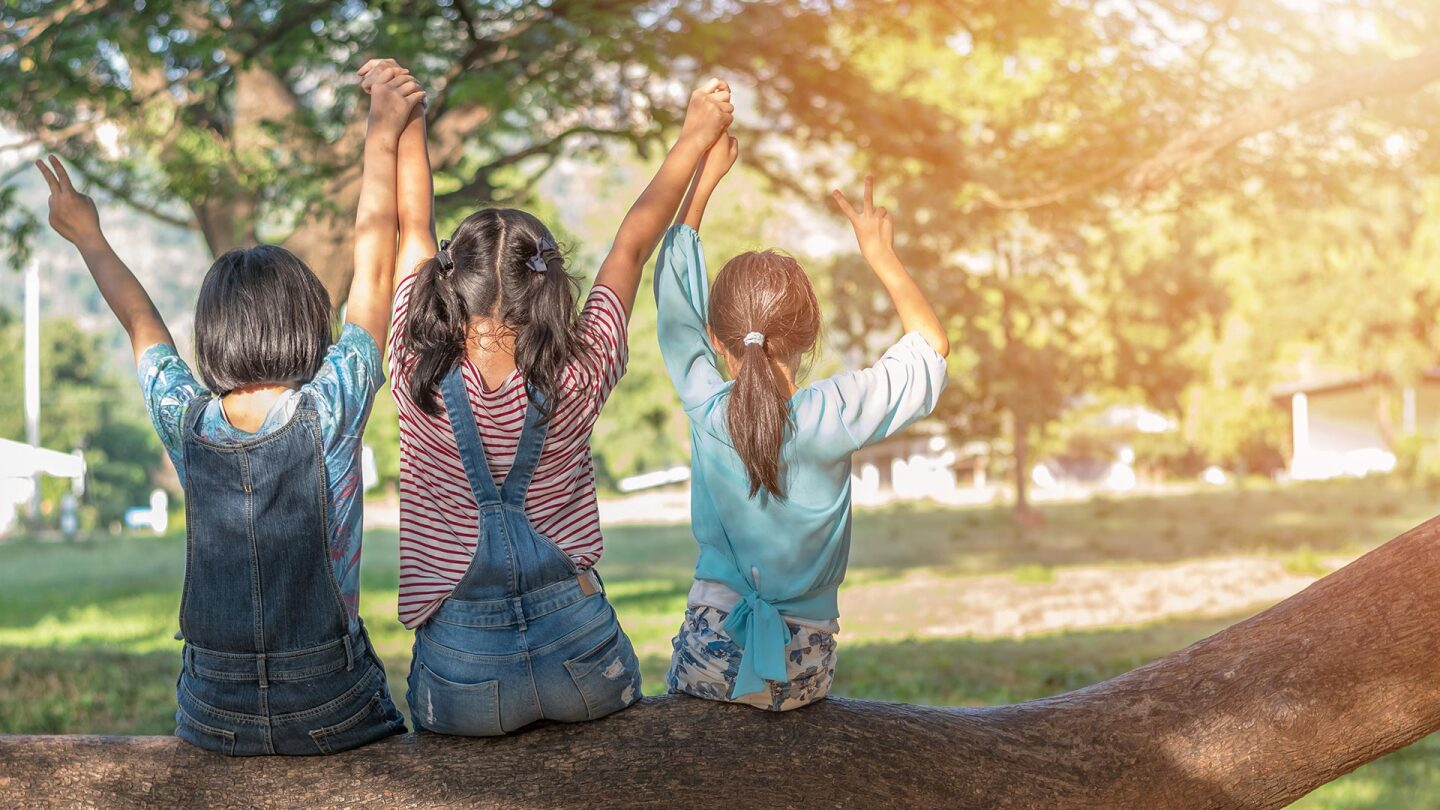 Three young girls sit on a tree facing away from the camera as they raise their hands together to the sky. | iStock