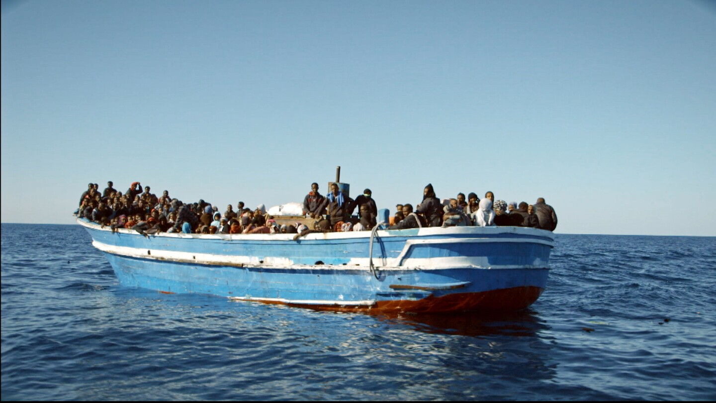 "A wooden boat overloaded with refugees from Libya, in the documentary ""Drowning Letters"" by Paula Palacios. 