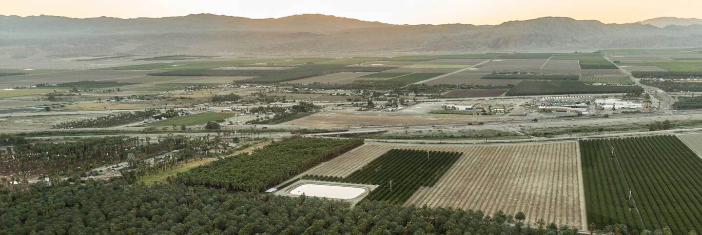 Aerial view of agricultural land against Coachella Valley mountains. | Lift to Rise