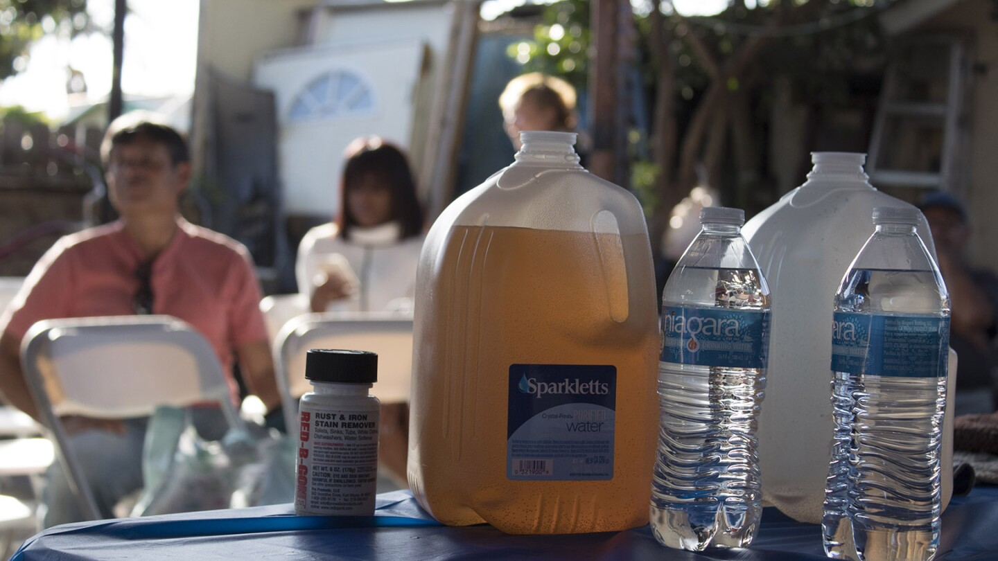 Brown water displayed on a table in Compton, CA from Sativa Water District