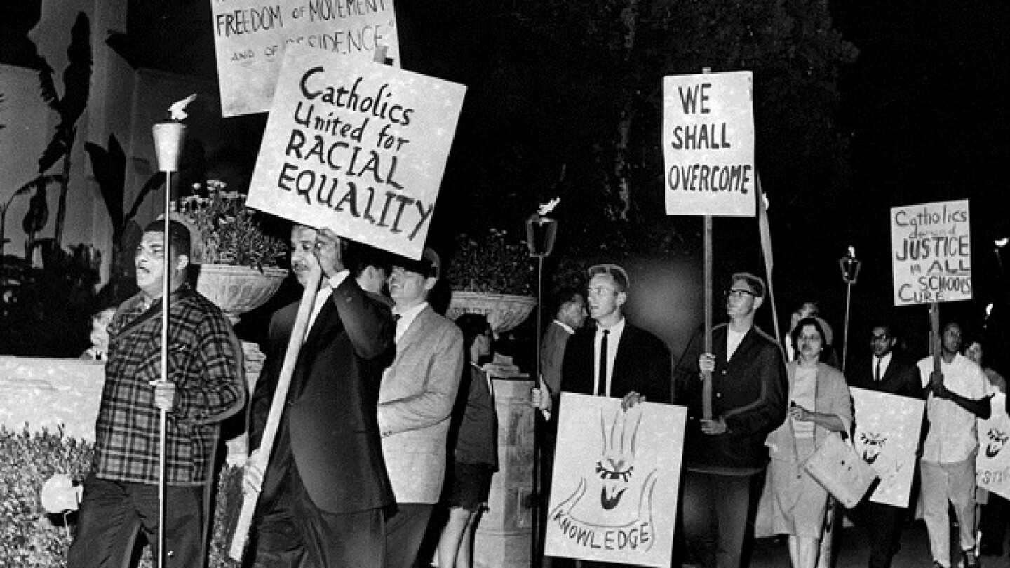 Carrying placards and lighted torches on May 18, 1964, protesters picket the entrance to Fremont Place in Los Angeles.