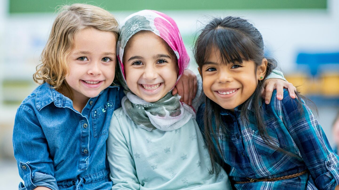 Three little girls, one blond, another wearing hijab and another with black hair, hug each other and smile.