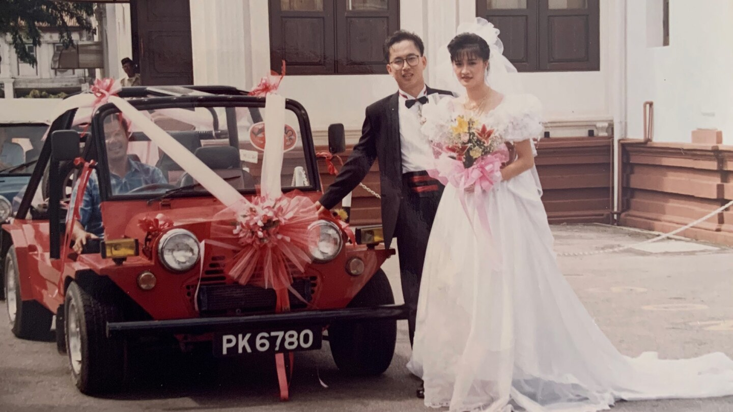 A bride and groom stand together and smile next to a little red car with a pink ribbon on it.