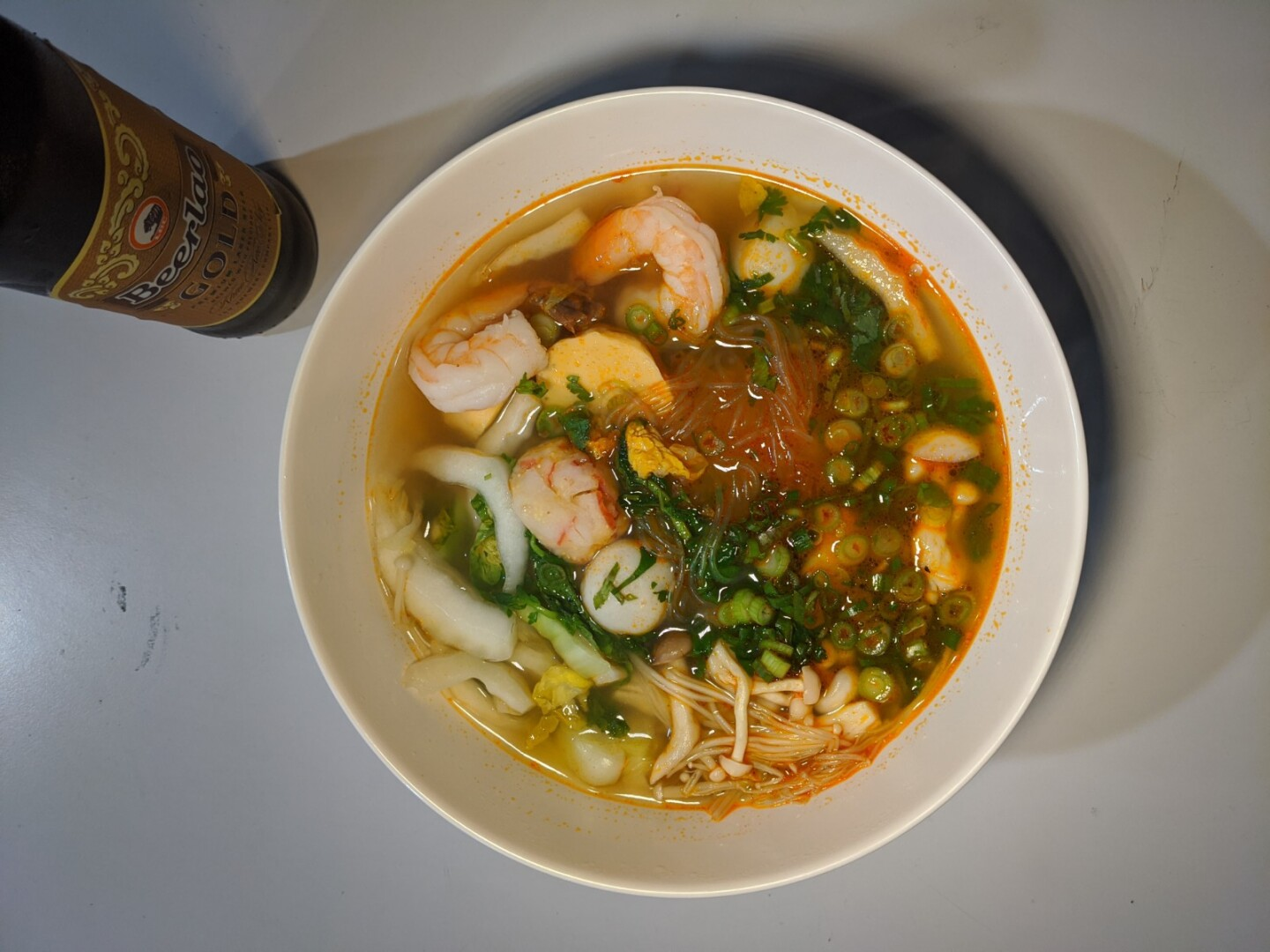An overhead shot of a bowl of sukiyaki, a mung bean noodle soup filled with various herbs, mushrooms, shrimp and noodles.