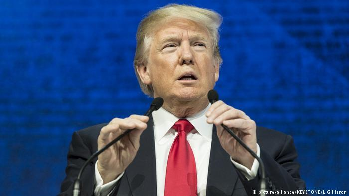 Donald Trump holding two microphones. | DW News
