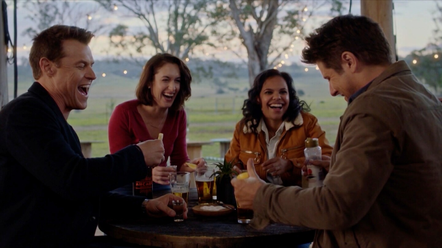 A group of four people share a laugh over drinks.