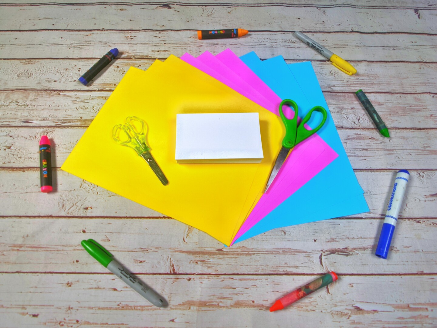 Colorful sheets of paper, index cards, scissors, crayons and markers are laid out on a table.