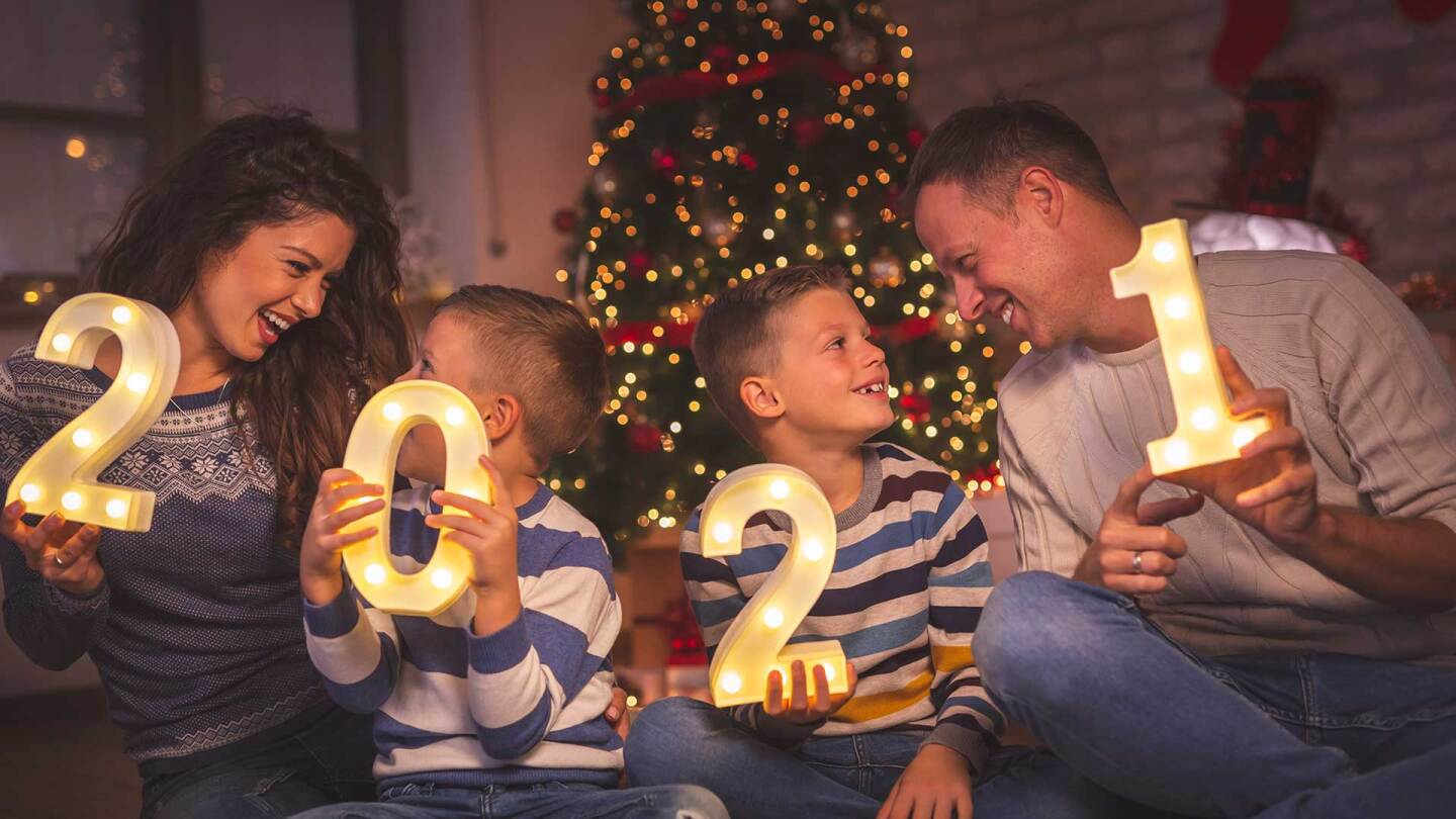 A family holds numbers counting down to the New Year.