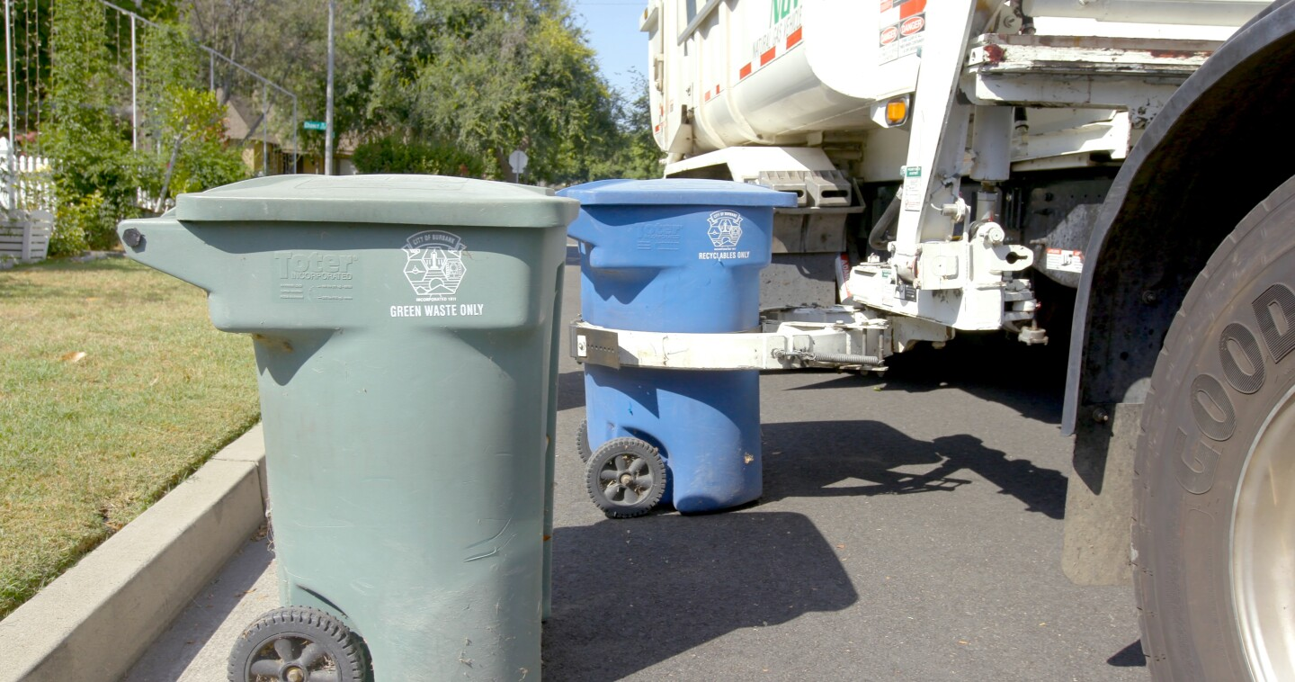 """Recycling bins being picked up by truck   Still from """"Life in Plastic: California's Recycling Woes"""""""