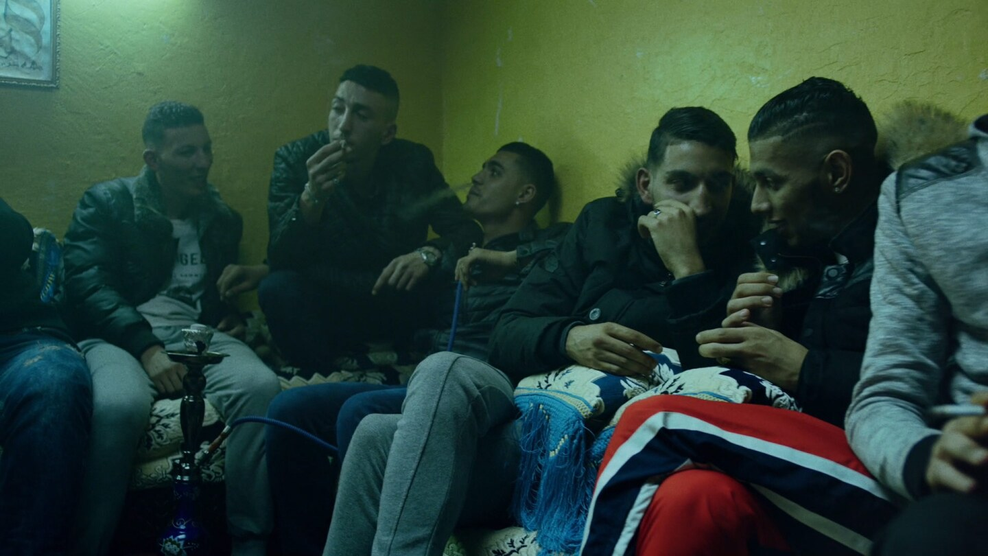 "Still from ""Territory:"" A group of people in a dimly lit room"