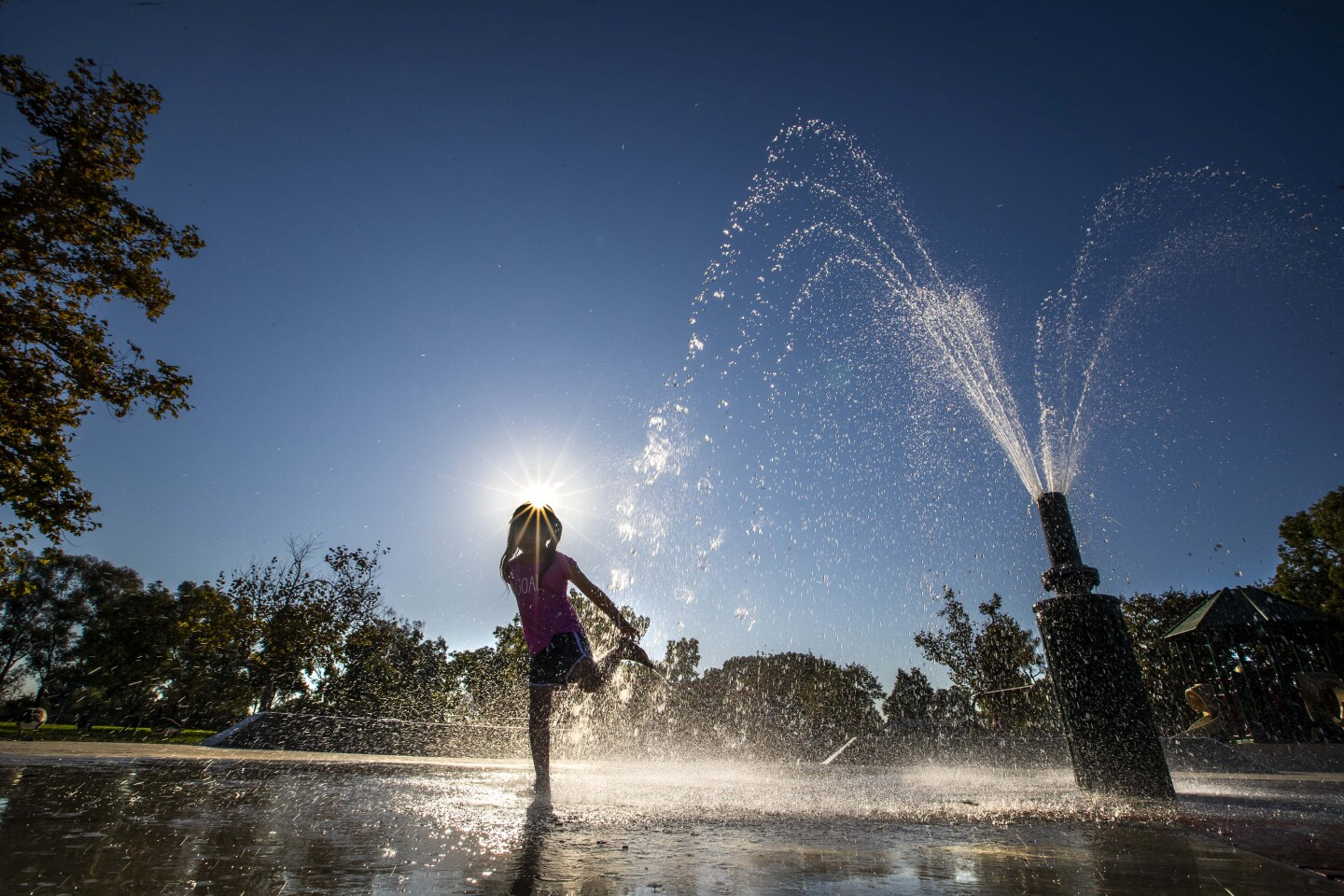 A girl playing in a fountain water at the park