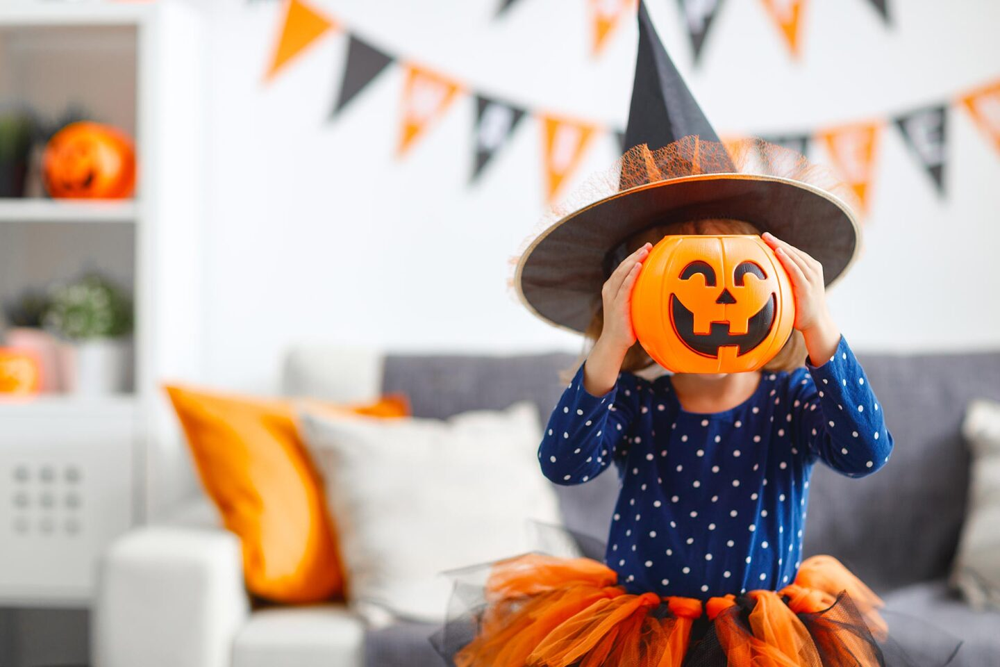 A little girl in a witch hat holds a plastic jack o' lantern over her face.