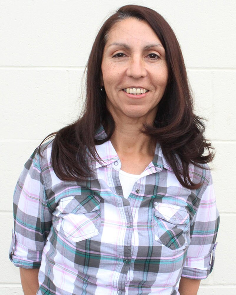 Frances Montoya wears her long brown hair down and smiles at the camera in a purple plaid shirt.