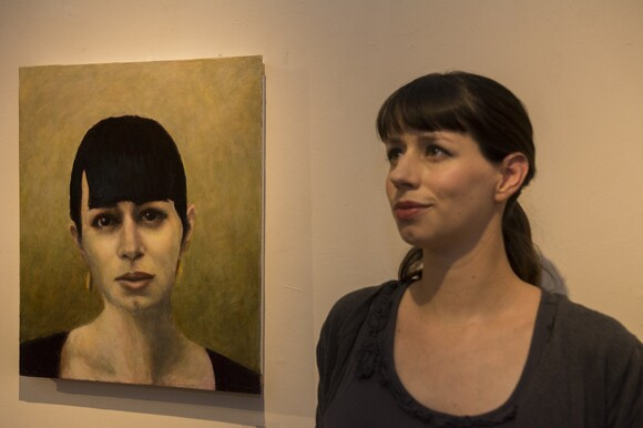 """The author poses with her portrait by David Settino Scott, featured in the exhibition """"Women"""" at the Steynberg Gallery in San Luis Obispo. 