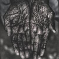 Wrinkled hands held out of someone in Bhubaneswar, India.