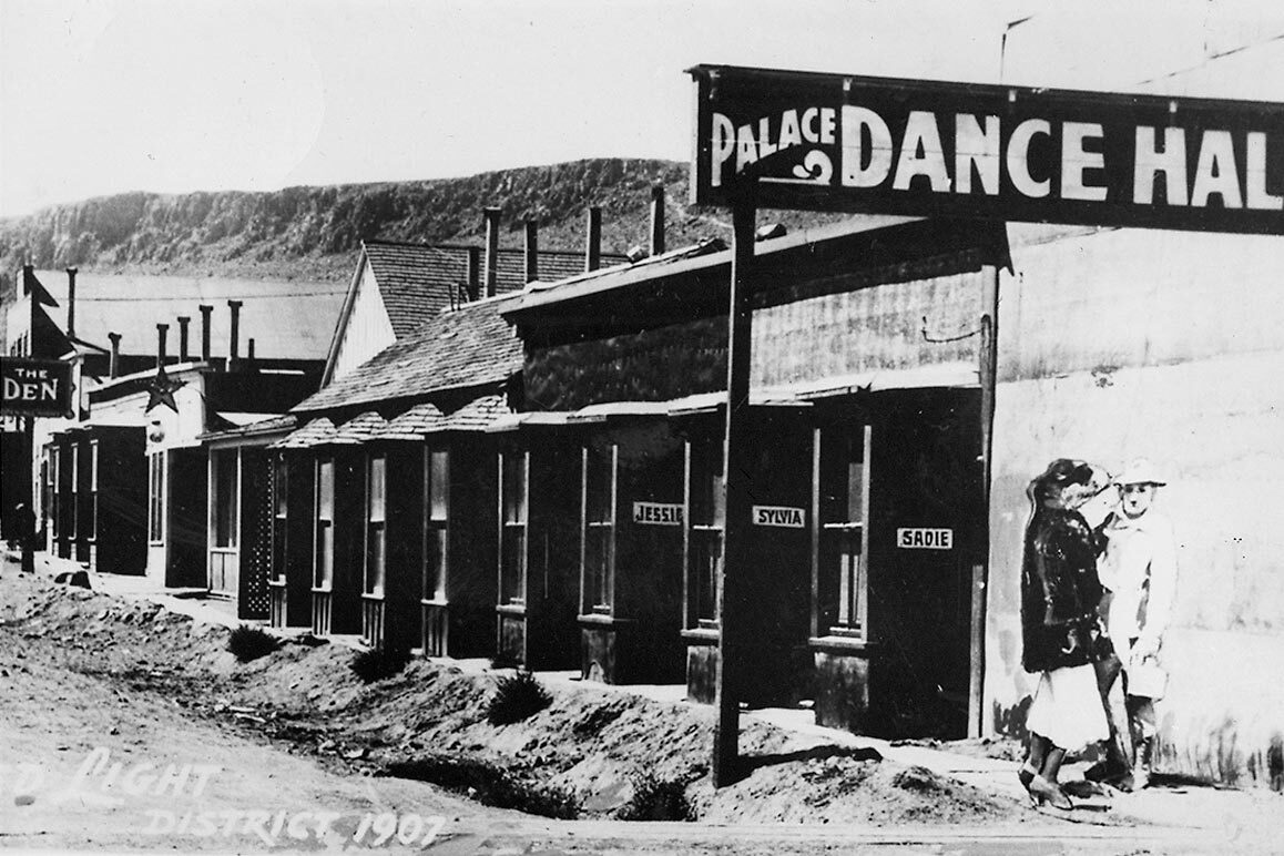 "Exterior of the Palace Dance Hall (a brothel). Sadie, Sylvia and Jessie are listed at the entries of three ""cribs"" where these women did business. 