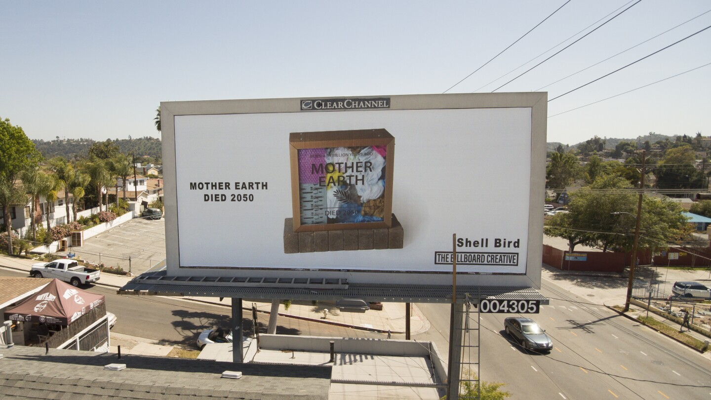 "A billboard shows a shadow box with a clear, see-through pane. On the transparent pane are the words ""Mother Earth"" printed on it. Inside the box are various pieces of trash and plastic. To the left of the box are the words, ""Mother Earth died 2050."""