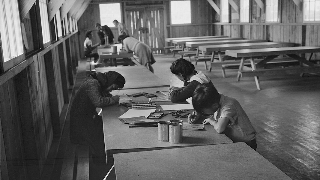 A black and white photo of Japanese American children painting at long wooden tables.