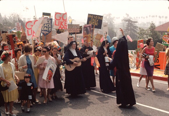 Sister Mathias (IHC choral director) leading Mary's Day Parade, Immaculate Heart College, Los Angeles, 1964. | Reproduction permission of the Corita Art Center, Immaculate Heart Community, Los Angeles.