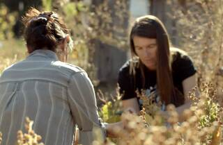 """Sara Moncada (Yaqui/Irish), chief program officer at the Cultural Conservancy, left, and Melissa K. Nelson (Turtle Mountain Chippewa), president and CEO of the Cultural Conservancy, right, tending plants together. 