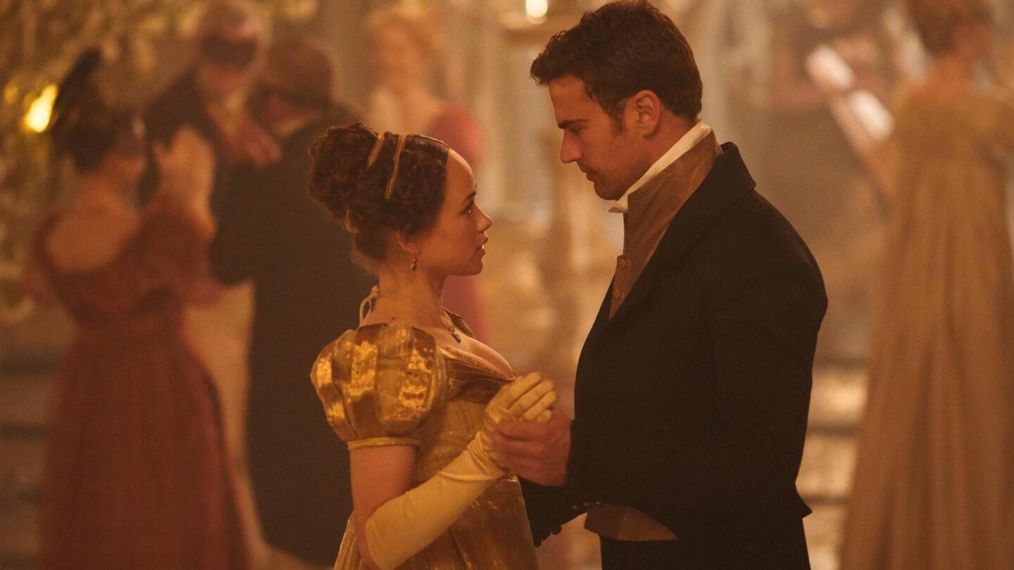 """A man and woman face each other in a ballroom. 