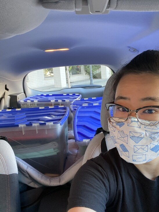 A face masked, bespectacled woman takes a selfie in her car, which contains materials to make cloth face masks.