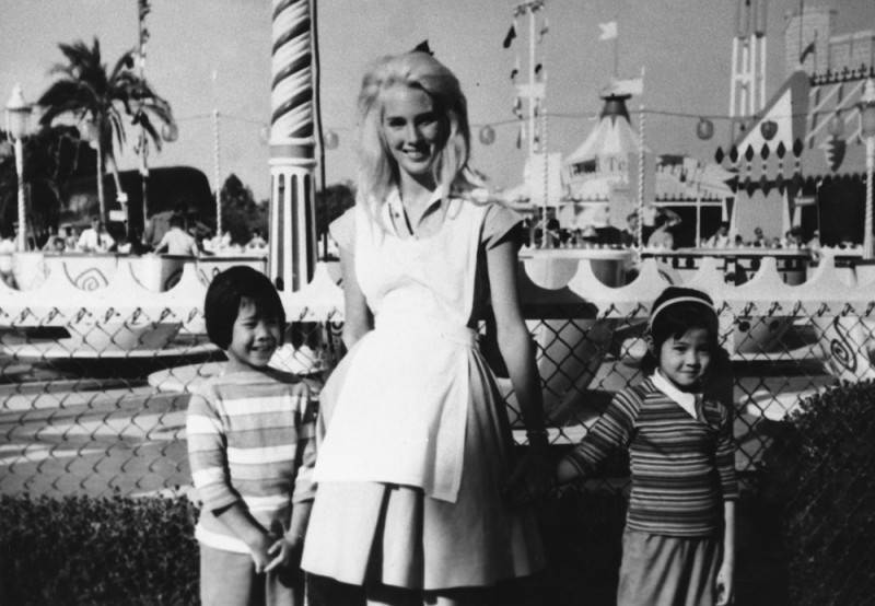 Two Chinese American girls pose with a woman dressed up as Alice in Wonderland at Disneyland