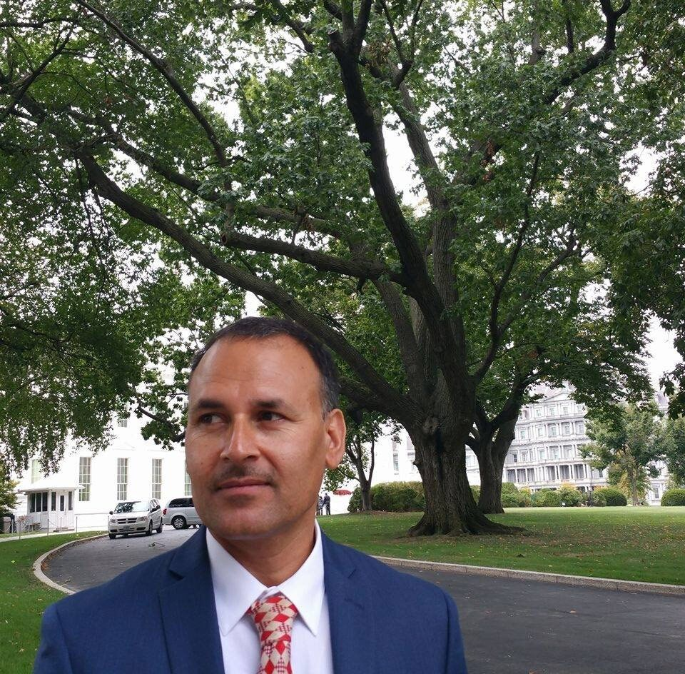 A man in a blue suit and red and gold tie stands in front of a tree.