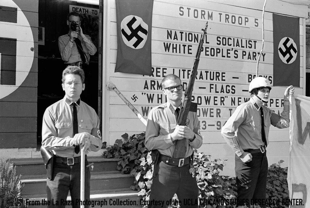 CSRC_LaRaza_B13F10S1_N020 National Socialist White People's Party stand armed outside a party chapter | Pedro Arias, La Raza photograph collection. Courtesy of UCLA Chicano Studies Research Center