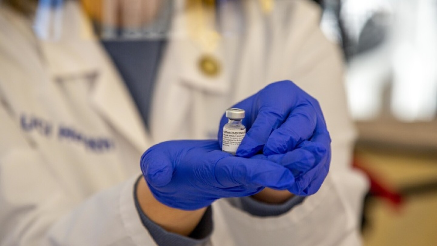 Close up of a pharmacist at UCI Health holding a dose of the COVID-91 vaccine.