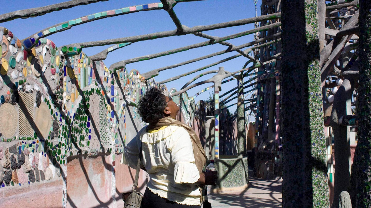 A woman looks up to appreciate the Watts Towers,