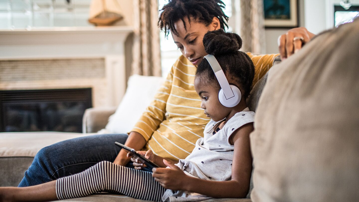Mother and daughter on couch using tablet
